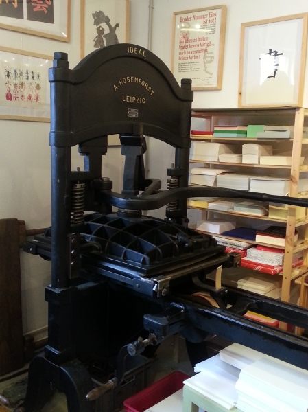 A Gutenberg-style press. The handheld-lever made  printing easier than older wheel cranking presses. However, because it printed one sheet at a time manually, the text was often off-center from page to page and on either side of a page.